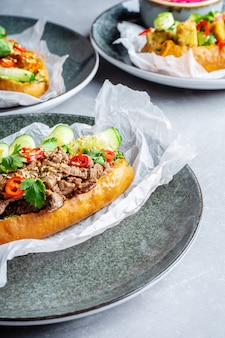 Set of banh-mi sandwich with sweet and sour chicken, veal, tofu, parsley, cucumber and chili pepper