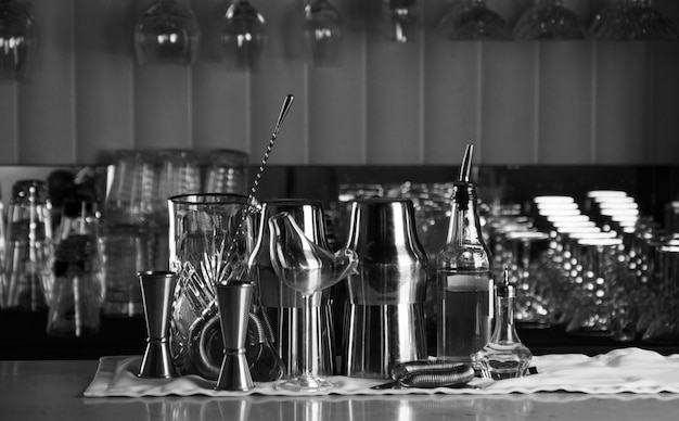 Set of bar accessories for making cocktails, located on the bar, behind is a shelving with liqueurs and strong alcohol. mixed media