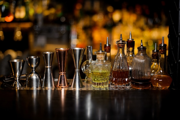 Set of barman tools including jiggers and little bottles with liquor