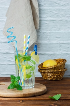 Set of basket with lemons, white cloth, cutting board and glass of lemon juice on a wooden and white surface. side view.
