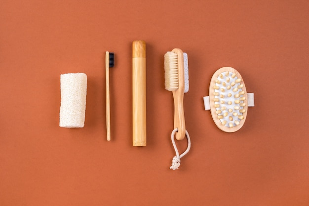 Set of bathroom accessories. anti cellulite massager, bamboo toothbrush, loofah sponge, peeling brush on brown. zero waste concept. minimalistic style.
