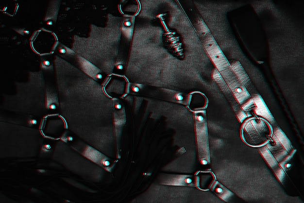 Set for bdsm sex in a sex shop. metal anal plug, leather whip flogger, belt and choker . black and white with glitch effect