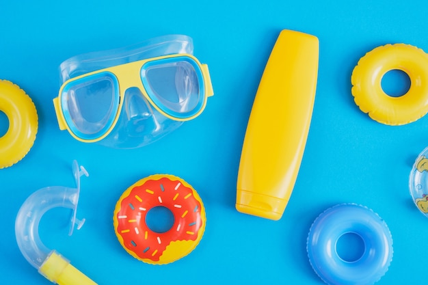Set for beach recreation and diving, sun cream or sun protection and toy inflatable circles on a blue background, mock up blank yellow cream bottle
