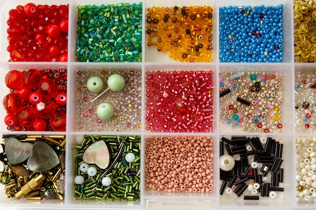 Set of beads of different colors, shapes, sizes in container
