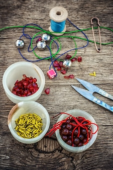 Set of beads in stacks on wooden table with tools for needlework.