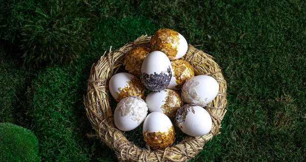 Set of beautiful easter eggs in a decorative nest on the moss