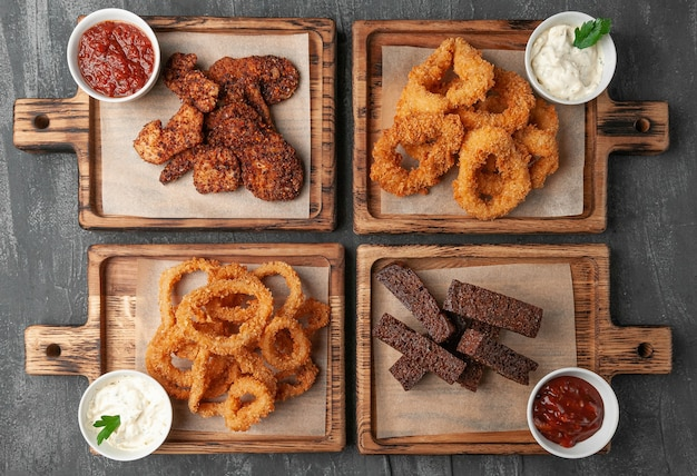 Set of beer snacks. consisting of spicy chicken chips, fried squid, croutons and onion rings in batter. with various sauces. . served on wooden boards. view from above. gray concrete background.