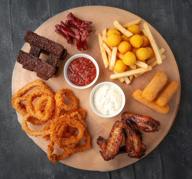 Set of beer snacks consisting of spicy chicken wings french fries cheese sticks squid in batter