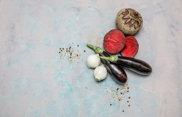 Set of beetroot, onions and eggplants on textured surface. top view. free space for your text