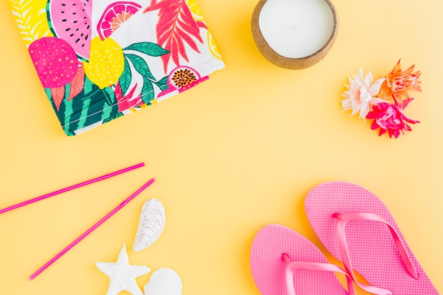 Set of belongings for exotic beach vacation on yellow background