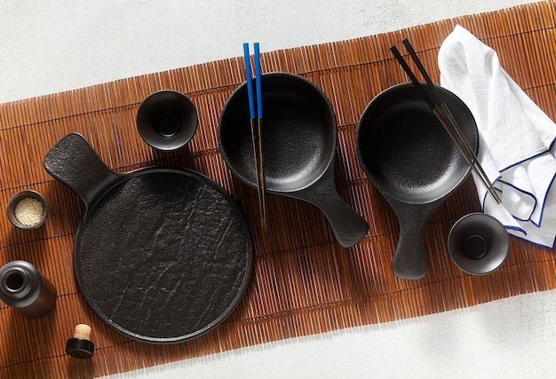 Set of black empty japanese breakfast tableware on bamboo mat