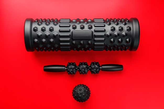 Set of black lumpy foam massage roller, body roller and rubber ball