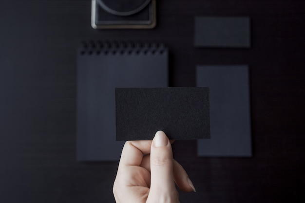 Set of black mockups on dark,  female hand holding a business card