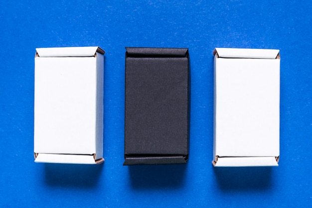 Set of black and white carton boxes on blue table, top view, flat lay