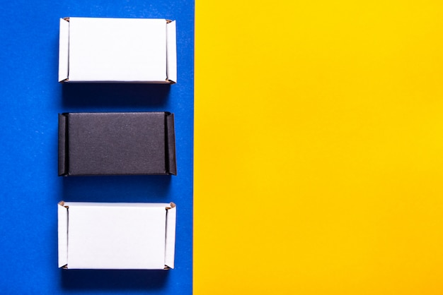 Set of black and white carton boxes on blue and yellow table, top view, copy space