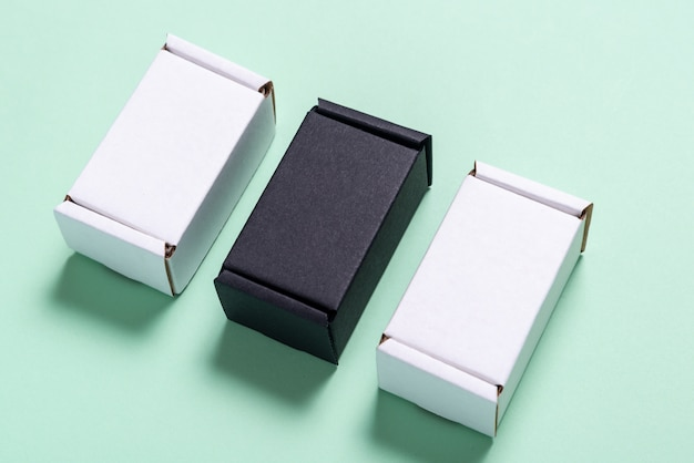 Set of black and white carton boxes on light green table, top view, flat lay
