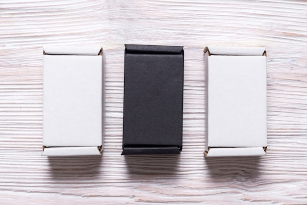 Set of black and white carton boxes on wooden table, top view, flat lay