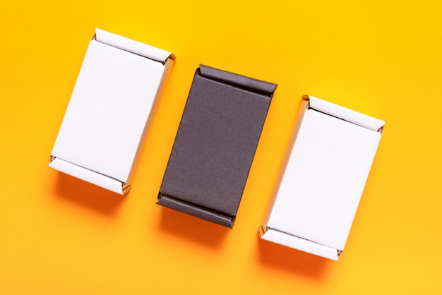 Set of black and white carton boxes on yellow table, top view, flat lay