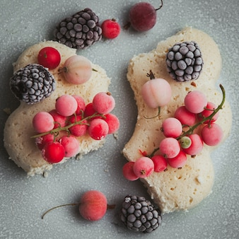 Set of blackberries, cookie and cranberries in a plate on a textured.