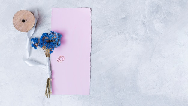 Set of blooms near paper, rings and bobbin of tape