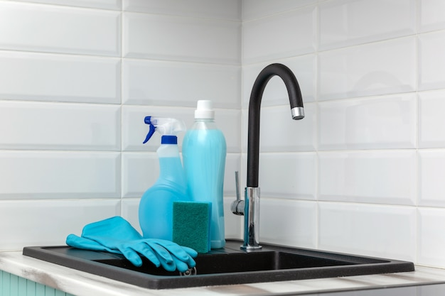 A set of blue cleaning products and tools for cleaning the kitchen is near the kitchen sink.