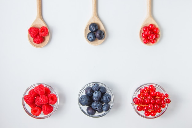 Set of blueberries and raspberries in a spoons and saucers
