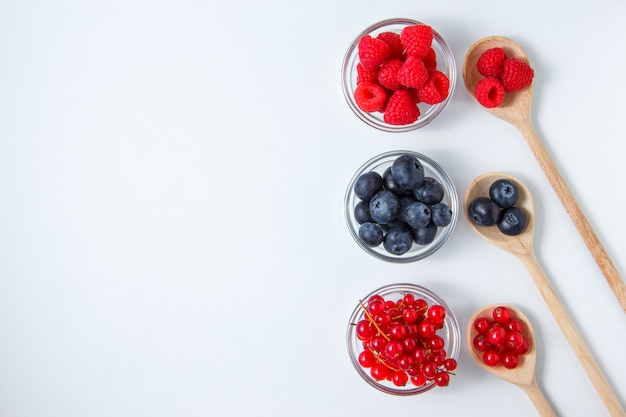 Set of blueberries and raspberries in a spoons and saucers.
