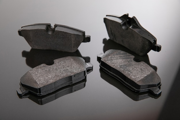 Set of brake pads on a mirror background