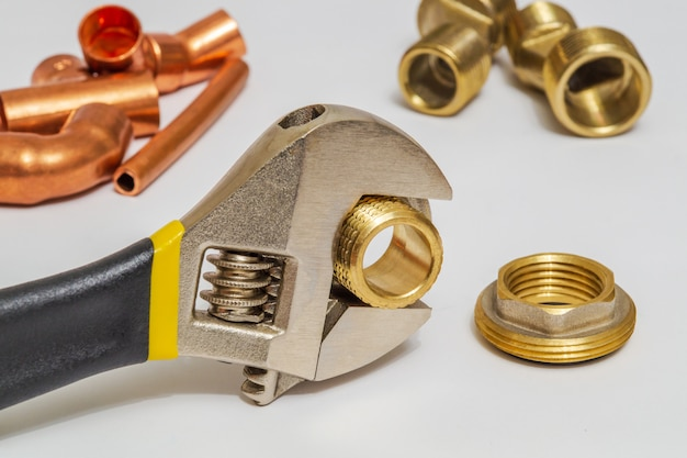 Set of brass fittings and tool is often used for water and gas installations on gray space
