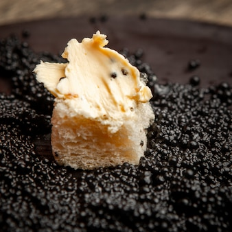 Set of bread and butter and black caviar on a dark background. high angle view.