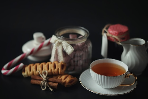 Set for breakfast. sweets and pastries with nuts for tea on black background. a coffee cup and patties.