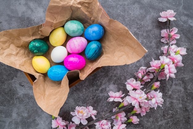 Set of bright easter eggs on craft paper in bowl near flower twig