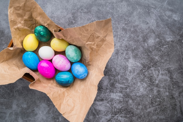 Set of bright easter eggs on craft paper in bowl