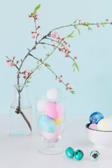 Set of bright easter eggs near flower twig in vase with water and bowl