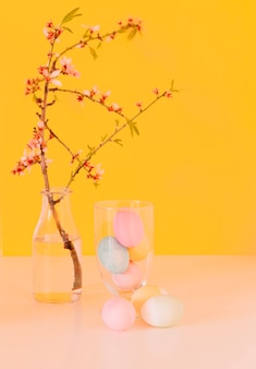 Set of bright easter eggs near flower twig in vase with water