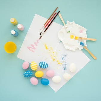 Set of bright eggs near papers and colors