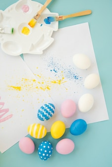 Set of bright eggs near sheets and brushes