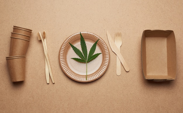 Set of brown paper plates, cups and wooden forks and knives on a brown background, flat lay.