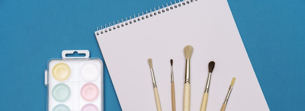 A set of brushes a sketchbook and bright watercolors on a blue background the concept of creativity