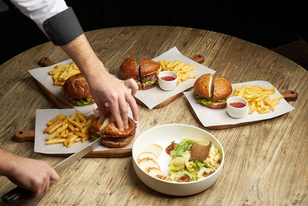 Set of burgers with french fries and ketchup sauce. big hamburgers and french fries on wooden table background. fast food set background. restaurant burger menu