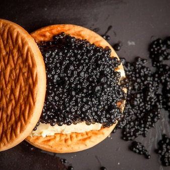 Set of butter and black caviar between biscuits on a dark background. top view.