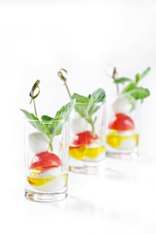 Set of canapes in glass with mozarella, tomato and olive oil greece salad