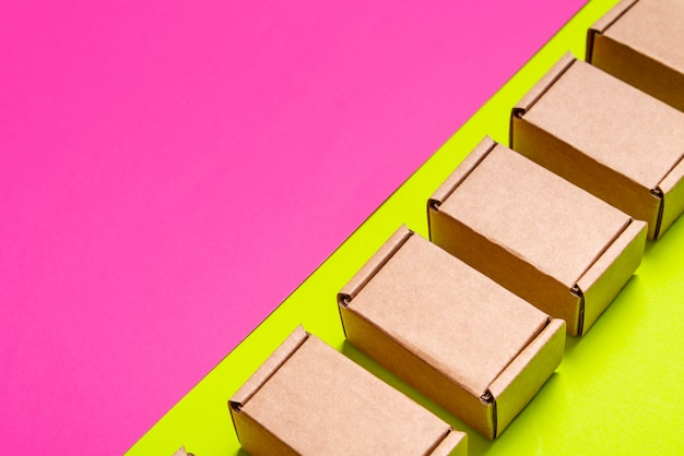 Set of cardboard boxes on pink, green background