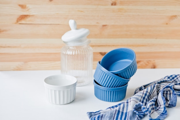 Set of ceramic dishes: small plates and glass jar on wooden table
