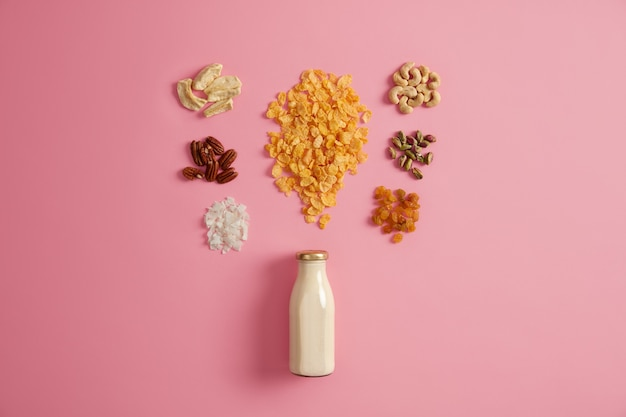 Set of cereals, pistachio, raisins, pecan nuts, dried apple, cashew, coconut around bottle of milk isolated on pink background. nourishing breakfast rich in vitamins to consume, nutrition concept.