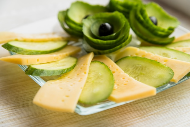 Set of cheese, cucumber and avocado with olives on dish on table