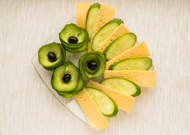 Set of cheese, cucumber and avocado with olives on plate