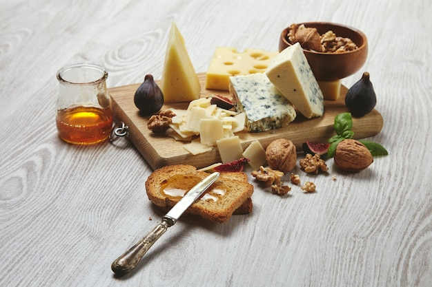 Set of cheeses on rustic cutting board isolated on side of brushed white wooden table, served for tasty breakfast with figs, rustic honey, dry bread and walnuts in bowl with basil leaves