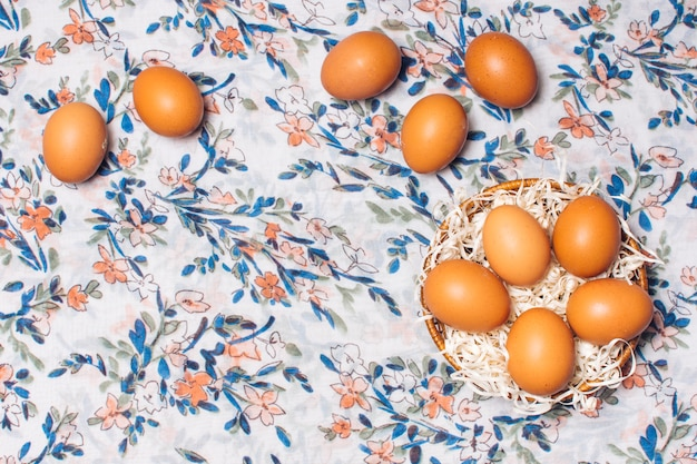 Set of chicken eggs in bowl on flowered material