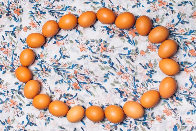 Set of chicken eggs in oval form on flowered material